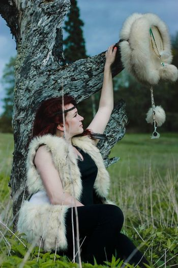 Full length of young woman with bird on grass