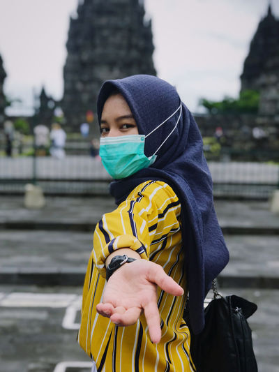Portrait of young woman wearing mask gesturing outdoors