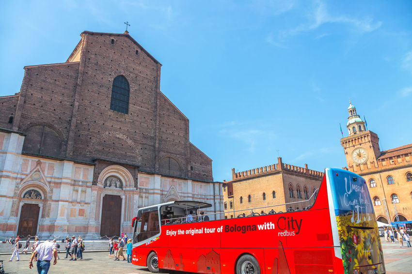 Bologna, Italy - May 28, 2016: Palazzo Re Enzo, historical landmark palace and heart of economic and social activities of the city with many people and the main square called Piazza Maggiore. People walking in via Rizzoli, restricted traffic zone, closed to traffic during the day on Saturday. The Two Towers, icons of Bologna, on background. Tourist train at side of Palazzo dei Banchi in Piazza Maggiore. San Luca Espress is the tourist line which connects the historic center with the Basilica of San Luca. Bologna Bologna, Italy Cathedral Church City Piazza Maggiore San Luca Tourist Arch Architecture Asinelli Asinelli Tower  Belief Building Building Exterior Built Structure City Day Group Of People History Italian Italy Mode Of Transportation Nature Outdoors People Place Of Worship Red Religion San Petronio Sky Street Streetphotography The Past Tourism Town Train Transportation Travel Travel Destinations