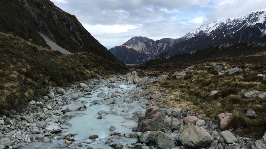 Scenic view of stream amidst mountains against sky