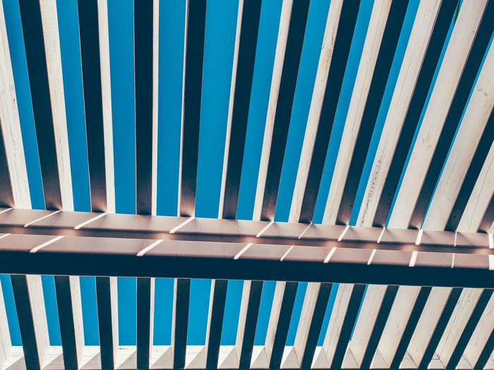Low angle view of railing against blue sky