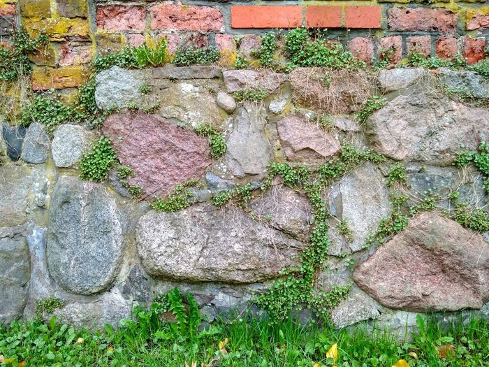 Close-up Day Outdoors No People Architecture Built Structure Brick Wall Building Exterior Backgrounds Textured  Pattern Full Frame Multi Colored Textured  Wall - Building Feature Stone Grass