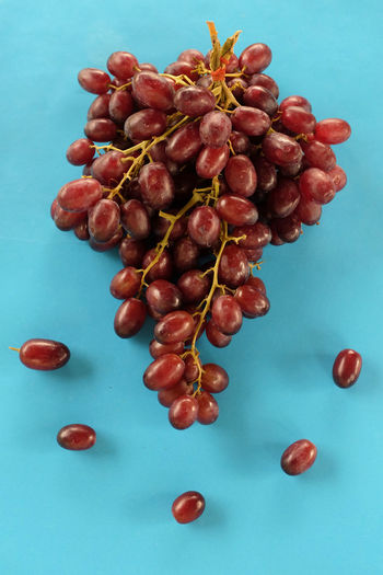 High angle view of grapes on table against blue background