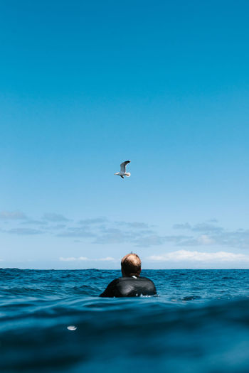 Man swimming in sea against blue sky