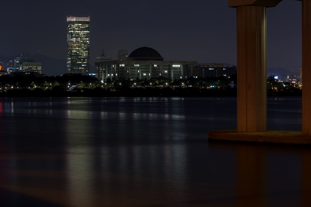illuminated, night, architecture, built structure, building exterior, travel destinations, no people, waterfront, water, city, sky, outdoors, skyscraper, cityscape, tree