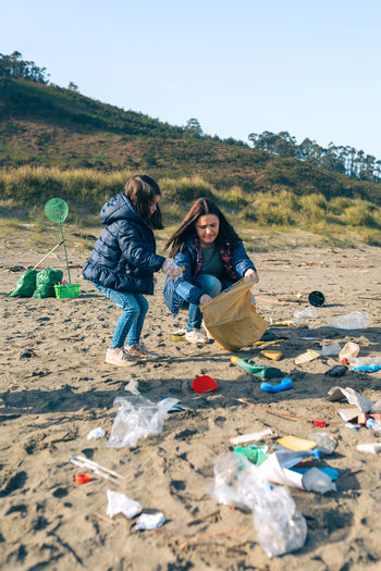 Mother and daughter picking garbage at beach