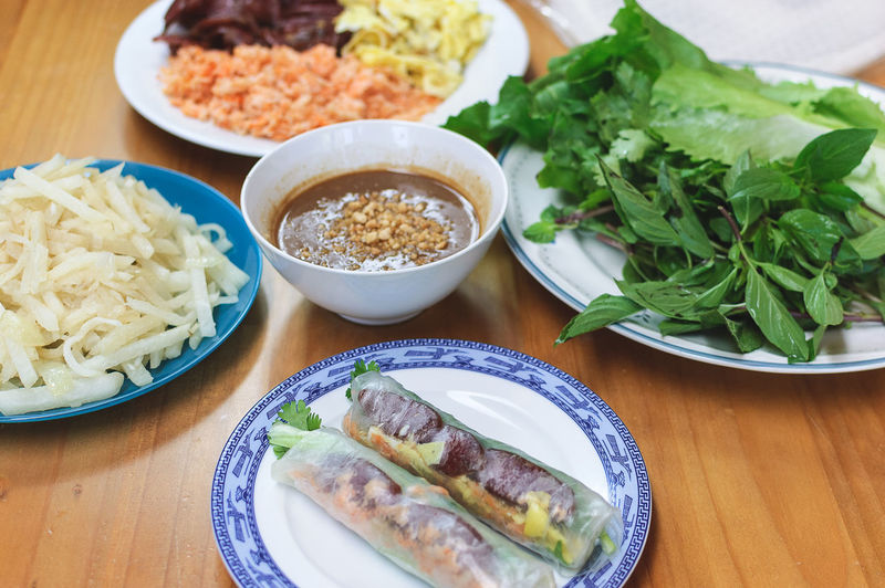 Ingredients for bo bia with 2 pieces made in the foreground Asian Food Bo Bia Bowl Close-up Dipping Sauce Food Food And Drink Freshness Healthy Eating Indoors  Ingredients Meal No People Peanut Butter Sauce Plate Ready-to-eat Rice Paper Rolls Table Vegetables Vietnamese Food