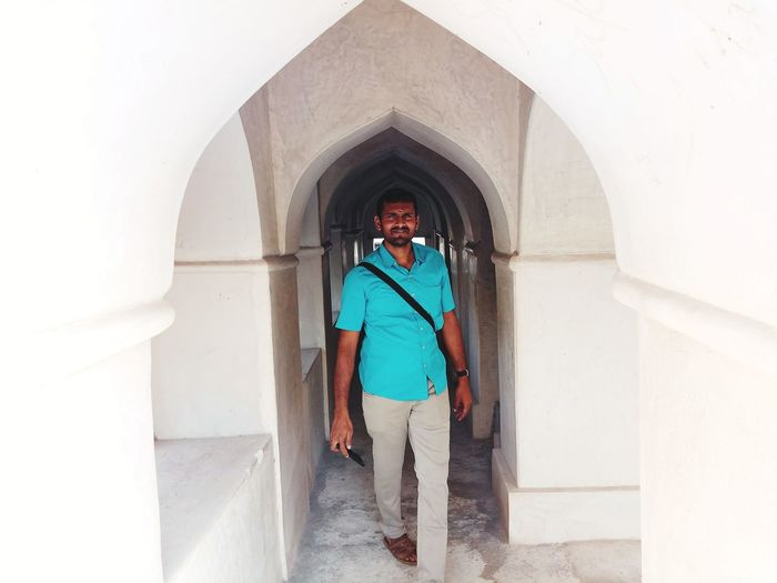 Full length of man walking in corridor on historic building