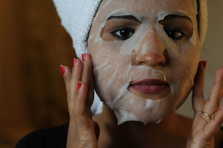 Portrait of woman using facial mask at home