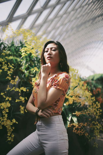Low angle view of beautiful woman standing by flowering plants in park