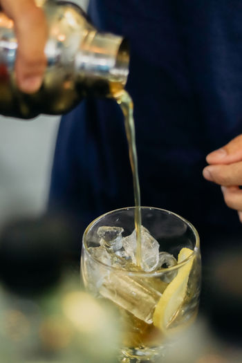 Cropped image of person pouring drink in glass