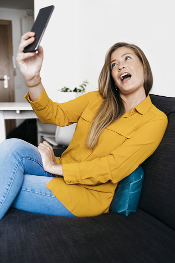 Young woman taking selfie with mobile phone while sitting on sofa at home
