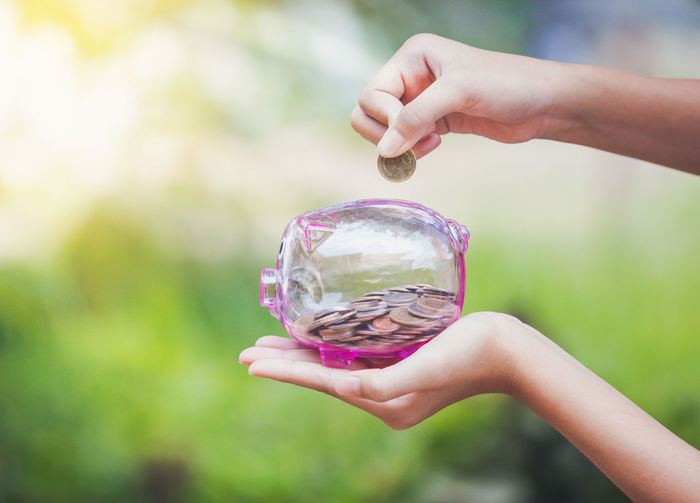 Close-up of person holding coin over transparent piggy bank