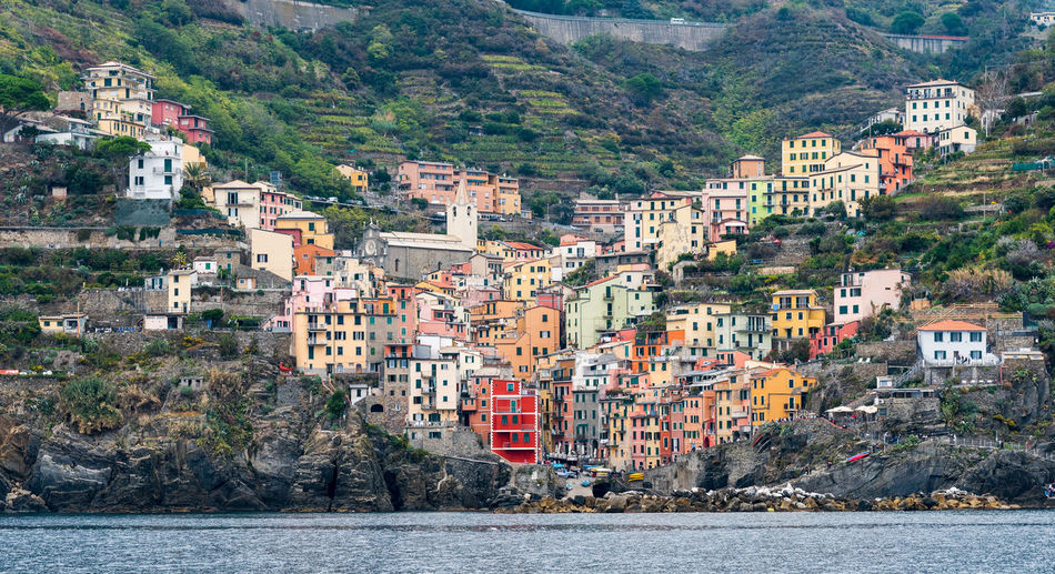 Village of Riomaggiore with colourful houses Seashore Architecture Building Building Exterior Built Structure City Coastal Day House Italy Land Mountain Nature Outdoors Plant Residential District Riomaggiore Sea Seascape Town TOWNSCAPE Tree View Into Land Water Waterfront