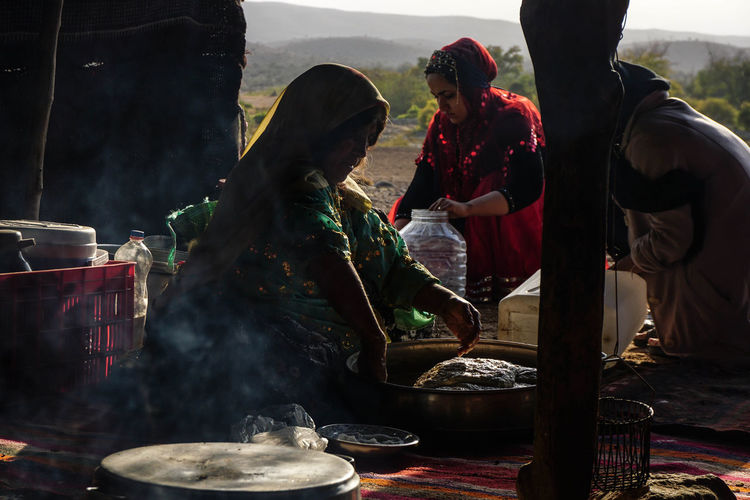 Iran Travel Destinations Travel Photography Nomadic Shia Community Travel Nomadic Life Real People Food Preparation  Food And Drink Market Occupation Day People Outdoors Business Smoke - Physical Structure Standing Belief Group Preparing Food Women Selling Market Stall