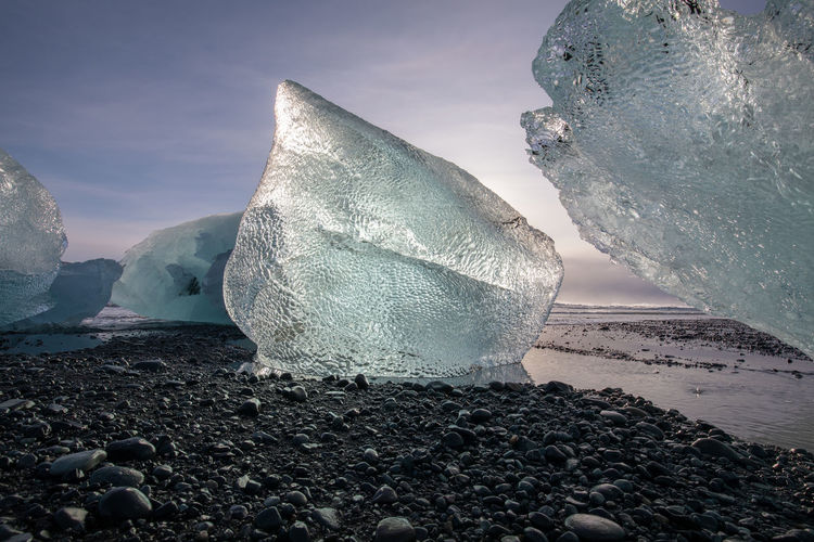 Surface level of frozen sea and rocks against sky