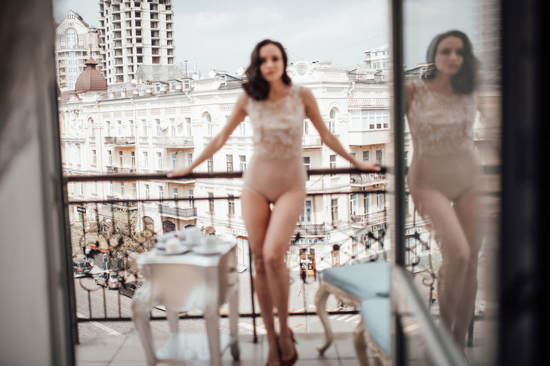 Full length of woman standing by balcony against cityscape
