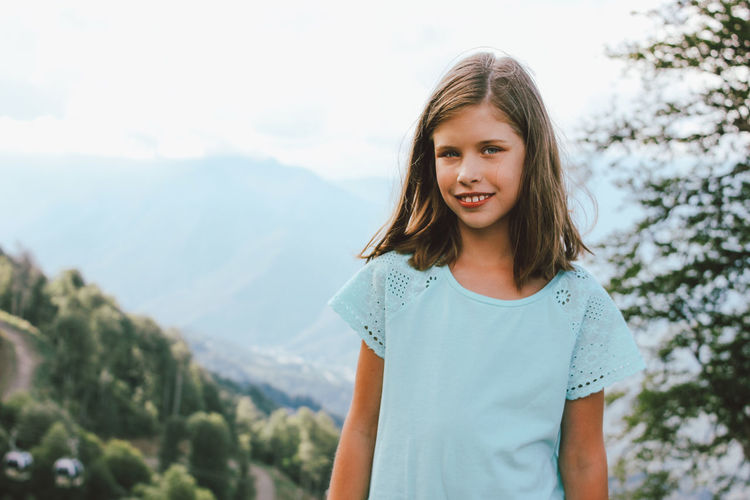 Portrait of smiling girl standing against mountains