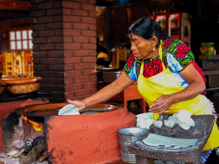 Senior woman cooking food in kitchen