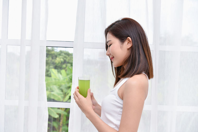 Side View Of Young Woman Holding Drink While Standing Against Window At Home