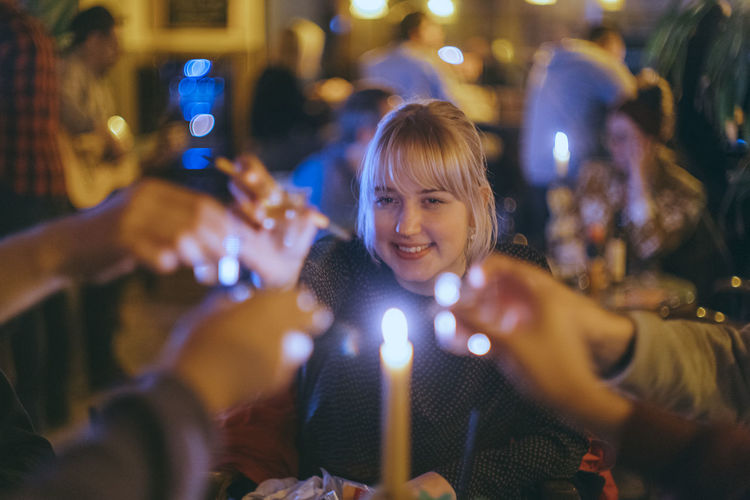 Portrait of smiling young woman with illuminated people at night