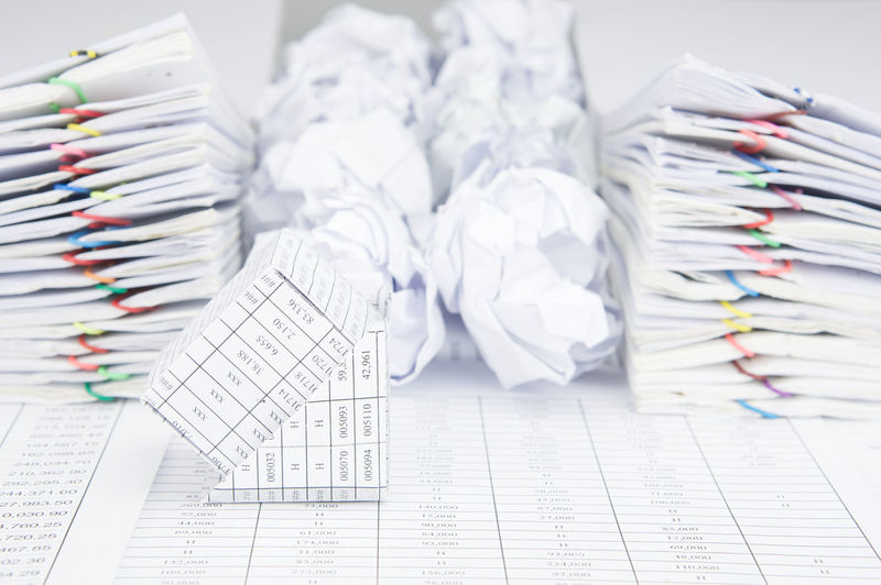 Close-up of crumpled paper balls and model house on financial documents