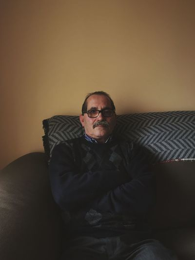 Portrait of mature man sitting on sofa against wall at home