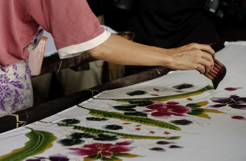 Cropped image of hand printing design on fabric at workshop