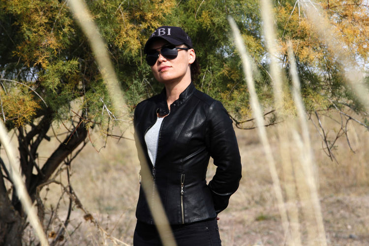 Portrait of woman wearing sunglasses and black jacket standing on field