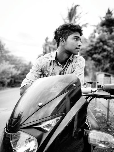 Young Man Sitting On Motorcycle Against Sky