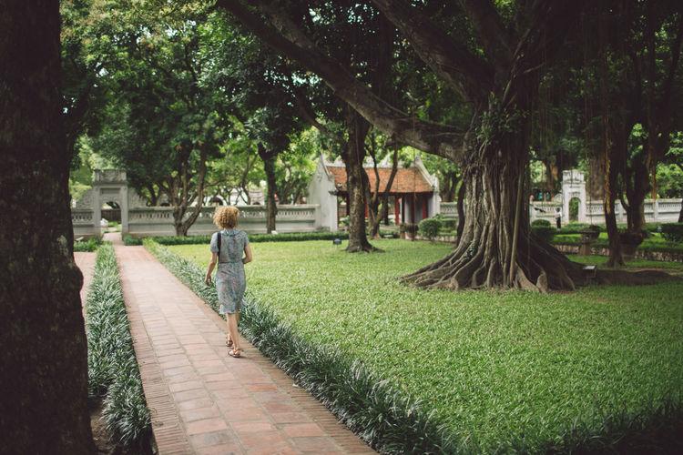 Rear view of woman walking on footpath in park