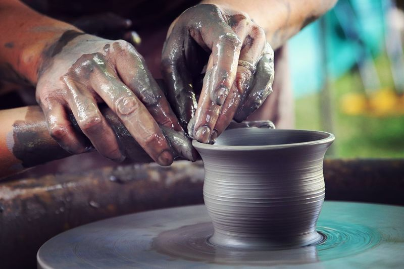 Cropped Hands Shaping Clay On Pottery Wheel