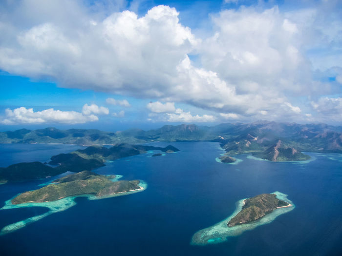 Aerial view of sea and mountains against cloudy sky