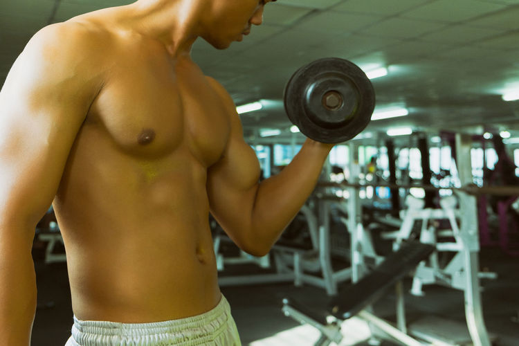 Shirtless man exercising at gym
