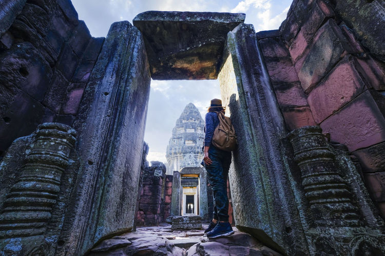 A tourist looking at ancient architecture and sculpture on vacation trip in pimai , thailand