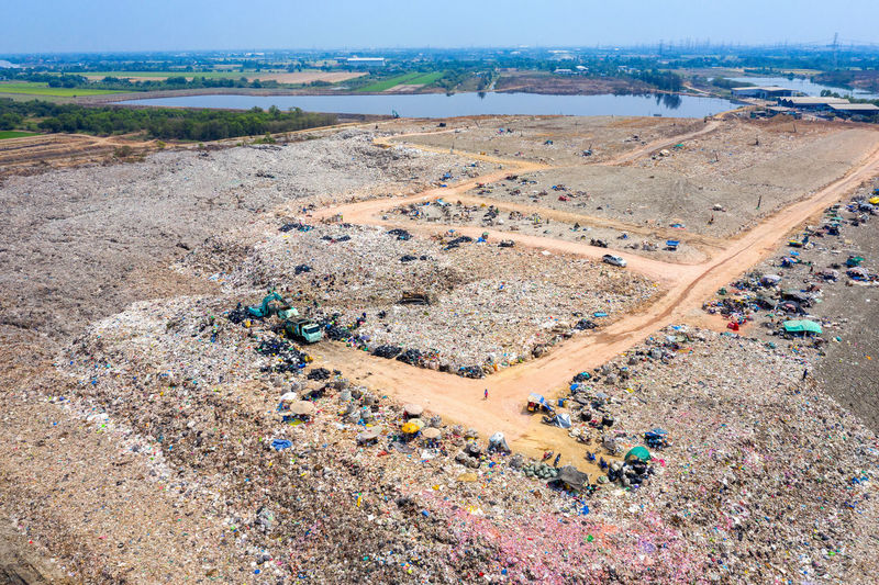 Aerial view of large landfill. Waste Garbage dump. High Angle View Environment Landscape Day Nature Land Outdoors Industry Aerial View No People Architecture Scenics - Nature Transportation Sunlight Plant Building Exterior Travel Destinations City Water Tranquility Pollution
