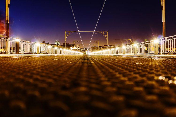 Illuminated railroad tracks against clear sky at night