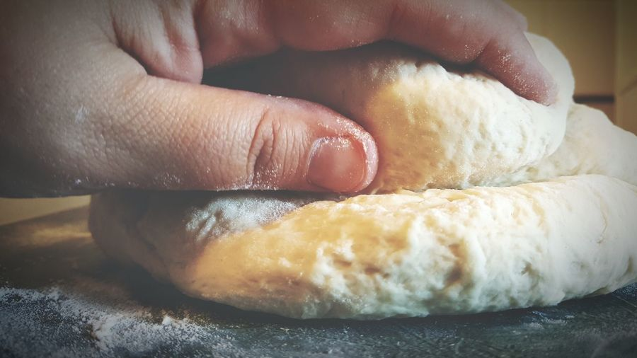 Cropped hand of woman kneading dough on table