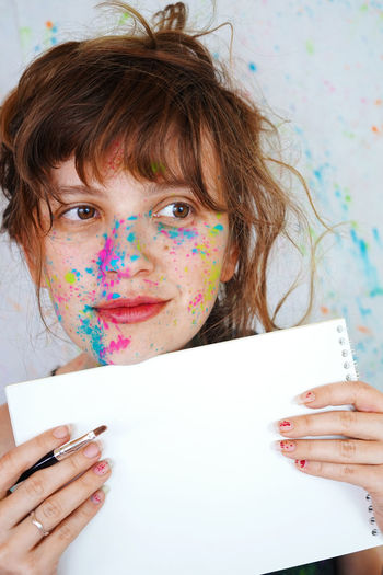 Close-up portrait of young woman holding text