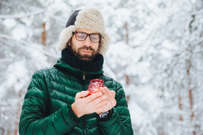 Portrait of young man holding ice cream cone during winter