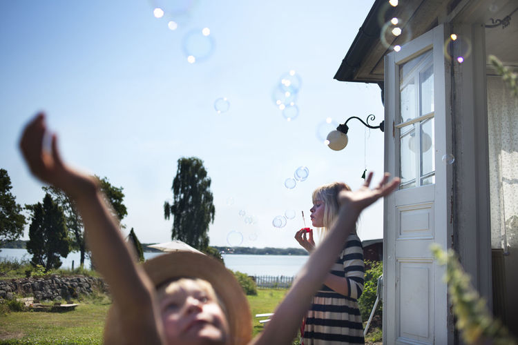 Low angle view of woman playing with bubbles in park against sky