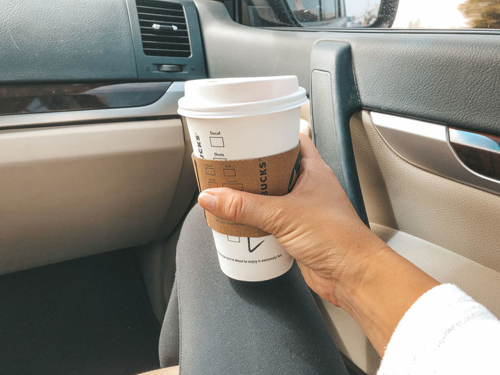 Human Hand Hand Vehicle Interior Human Body Part Transportation One Person Mode Of Transportation Real People Holding Car Interior Car Motor Vehicle Cup Drink Lifestyles Land Vehicle Coffee - Drink Food And Drink Coffee Body Part Finger