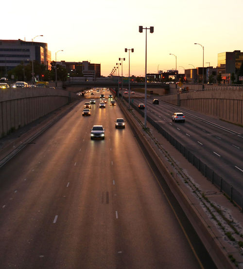 Vehicles on road at sunset