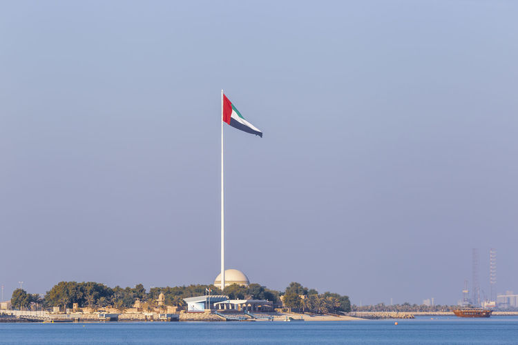 Flag in sea against clear sky