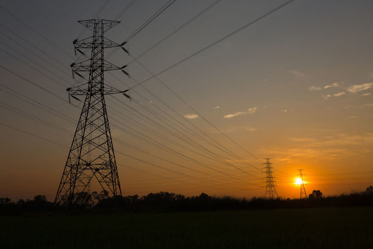 Low angle view of electricity pylon on field against sky during sunset