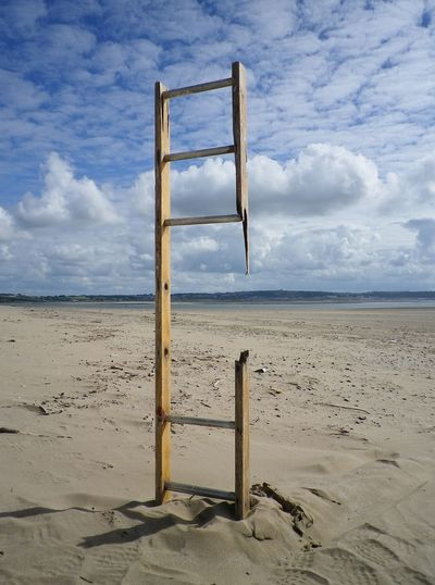 Close-up of broken ladder at beach against cloudy sky