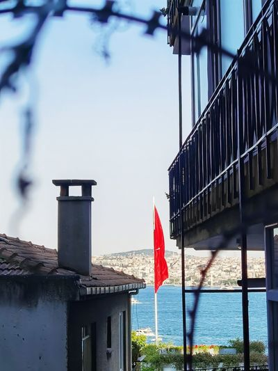 Low angle view of flag on building by sea against sky