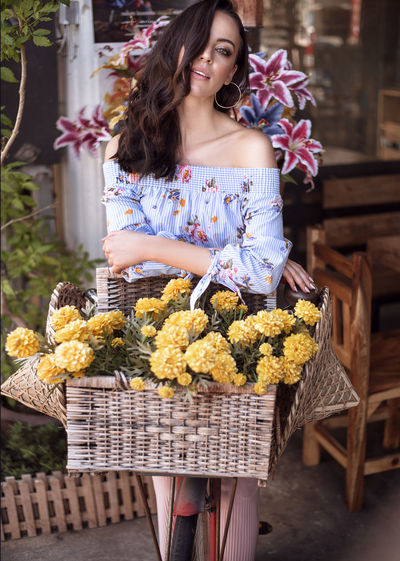 Portrait of woman holding flowers in basket standing outdoors