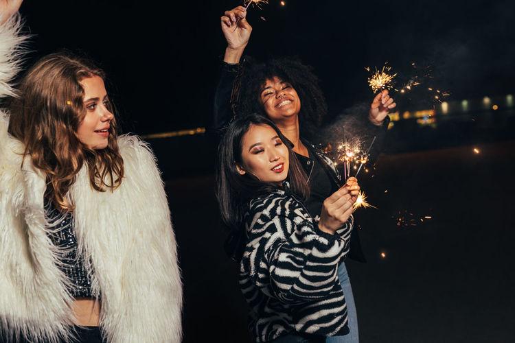 Smiling young women holding sparkler enjoying in night club
