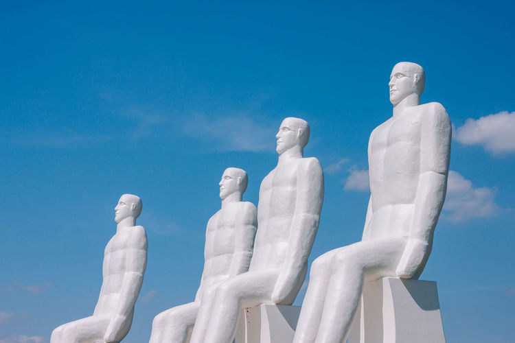 Low angle view of statues against blue sky during sunny day
